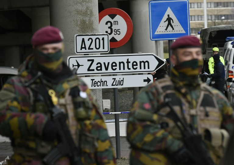 Soldiers stations in the Belgium capital of Brussels standing in front of a sign to Zaventem airport, March 29, 2016. (AFP/John Thys)