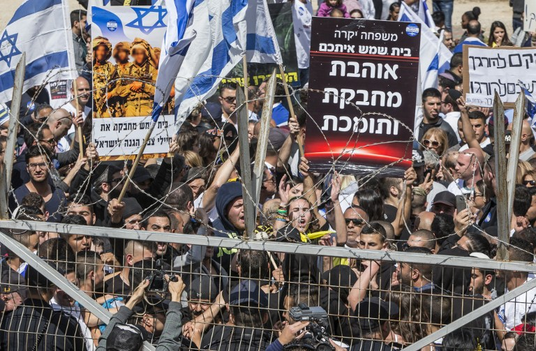 Demonstrators hold banners and flags outside an IDF court hearing in Kiryat Malakhi on March 29, 2016, to show their support for a soldier who shot a wounded Palestinian assailant in the head as he lay on the ground. (AFP / JACK GUEZ)