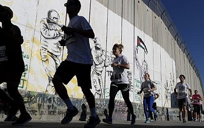 Participants run along Israel's security barrier in the West Bank town of Bethlehem during the 4th Palestine Marathon on April 1, 2016. (AFP/Thomas Coex)