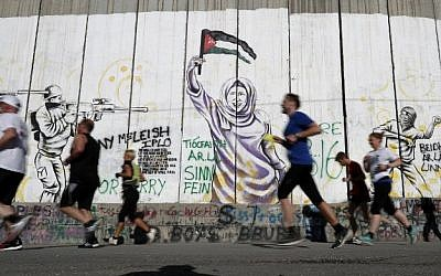 Participants run along Israel's security barrier in the West Bank town of Bethlehem during the 4th Palestine Marathon on April 1, 2016. (AFP / THOMAS COEX)