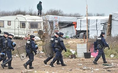 Policemen walk as people stand on a shelter's roof on  March 1, 2016 in the 'Jungle' migrants and refugees camp in the French northern port city of Calais during the dismantling of half of the camp. (AFP/Philippe Huguen)