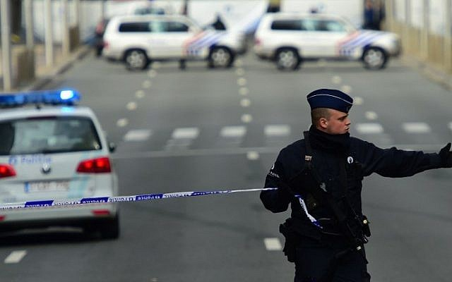 A police officers sets a security perimeter near Maalbeek metro station,  on March 22, 2016  in Brussels, after a blast at this station near the EU institutions caused deaths and injuries.  (AFP PHOTO / EMMANUEL DUNAND / AFP / EMMANUEL DUNAND)