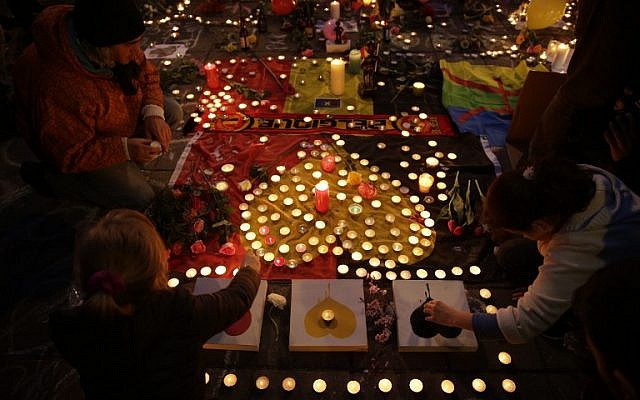 People light candles in tribute to victims at a makeshift memorial in front of the stock exchange at the Place de la Bourse (Beursplein) in Brussels on March 22, 2016, following triple bomb attacks in the Belgian capital that killed about 35 people and left more than 200 people wounded.(AFP PHOTO / KENZO TRIBOUILLARD)