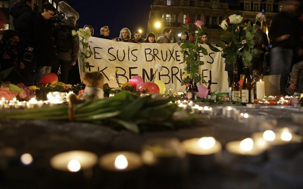 People hold a banner reading 'Je suis Bruxelles' (I am Brussels) in tribute to victims at a makeshift memorial in front of the stock exchange at the Place de la Bourse in Brussels on March 22, 2016.  (AFP  / KENZO TRIBOUILLARD)