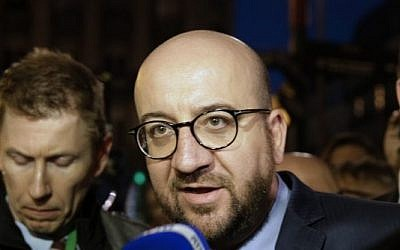 Belgian Prime Minister Charles Michel speaks to the press at a makeshift memorial in front of the stock exchange at the Place de la Bourse (Beursplein) in Brussels on March 22, 2016, following triple bomb attacks in the Belgian capital that killed about 35 people and left more than 200 people wounded. (AFP PHOTO / KENZO TRIBOUILLARD)