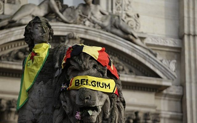 A Belgian flag is draped on a sculpture at a makeshift memorial on the Place de la Bourse (Beursplein) in Brussels on March 23, 2016, a day after blasts hit the Belgian capital. (AFP PHOTO/KENZO TRIBOUILLARD)