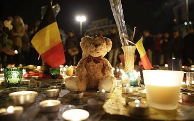 A Belgian flag, candles and a teddy bear are pictured as people gather at a makeshift memorial on the Place de la Bourse (Beursplein) in Brussels on March 23, 2016, a day after a triple bomb attack, which responsibility was claimed by the Islamic State group, left at least 30 dead and hundreds injured in the Belgian capital. (AFP PHOTO/KENZO TRIBOUILLARD)