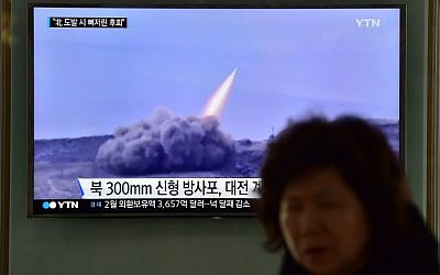 File: A woman walks past a public television screen showing file footage of a North Korean missile, at a railway station in Seoul, March 4, 2016. (AFP/JUNG YEON-JE)