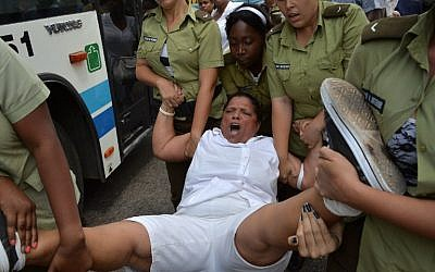 A member of the Ladies in White Human Rights organization is arrested during a march on March 20, 2016 in Havana, hours before the arrival of US President Barack Obama. (AFP PHOTO/ADALBERTO ROQUE)