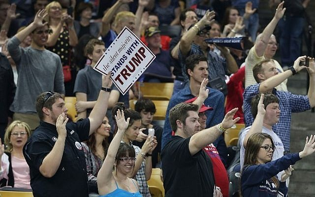 People raise their arms as Republican presidential candidate Donald Trump ask them to pledge that they will vote for him during a campaign rally at the CFE Arena on the campus of the University of Central Florida on March 5, 2016 in Orlando, Florida. ( Joe Raedle/Getty Images/AFP)