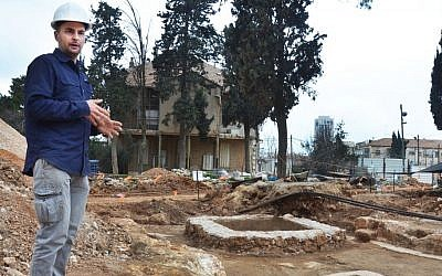Excavation director, Alex Wiegmann, alongside an ancient winery complex uncovered on the site of the former Schneller IDF base in Jerusalem. (Israel Antiquities Authority)