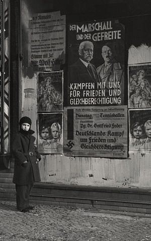 Mara Vishniac posing in front of a 1933 election poster for Hindenburg and Hitler that reads 'The Marshal and the Corporal: Fight with Us for Peace and Equal Rights' (© Mara Vishniac Kohn, courtesy International Center of Photography)