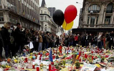 Three balloons in the colors of the Belgian flag fly as people mourn for the victims of the bombings at the Place de la Bourse in the center of Brussels, Belgium, Thursday, March 24, 2016.  (AP Photo/Peter Dejong)