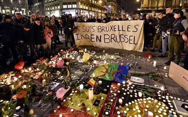 "People holding a banner reading ""I am Brussels"" behind flowers and candles to mourn for the victims at Place de la Bourse in the center of Brussels, Tuesday, March 22, 2016.  (AP Photo/Martin Meissner)"