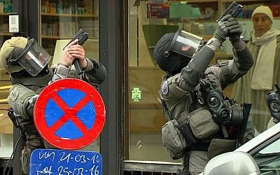 In this framegrab taken from VTM, armed police officers take part in a raid in the Molenbeek neighborhood of Brussels, Belgium, Friday March 18, 2016. (VTM via AP)