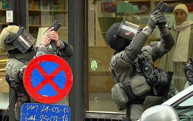 Armed police officers take part in a raid in the Molenbeek neighborhood of Brussels, Belgium, March 18, 2016. (screenshot: VTM via AP)