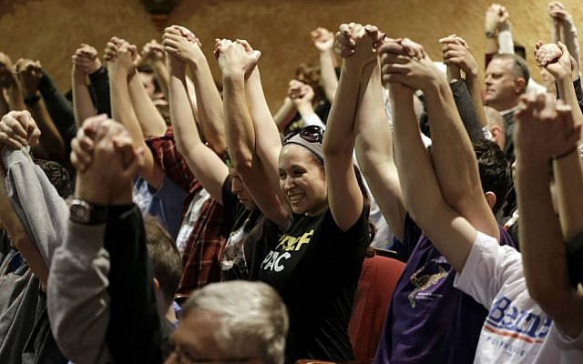 Supporters join hands during a prayer waiting for Democratic presidential candidate Sen. Bernie Sanders, I-Vermont, to speak at a campaign rally at the Akron Civic Theatre in Akron, Ohio, Monday, March 14, 2016. (AP Photo/Tony Dejak)