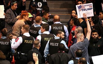 A demonstrator is removed by Chicago police during a rally for Republican presidential candidate Donald Trump at the University of Illinois at Chicago Pavilion in Chicago on Friday, March 11, 2016. Trump canceled one of his signature rallies on Friday, calling off the event in Chicago due to safety concerns after protesters packed into the arena where it was to take place. (Chris Sweda/Chicago Tribune via AP)