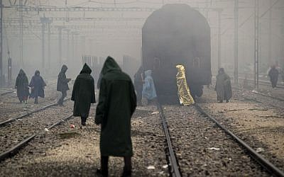 Migrants, one wearing a thermal blanket, walk on railway tracks at the northern Greek border station of Idomeni, Sunday, March 13, 2016. Bad weather returned after a brief pause and conditions in the refugee camp on the Greek-Macedonian where about 14,000 people are stranded have further deteriorated, many of its residents struggling struggling to cope with the many challenges posed by the heavy rain. (AP Photo/Vadim Ghirda)
