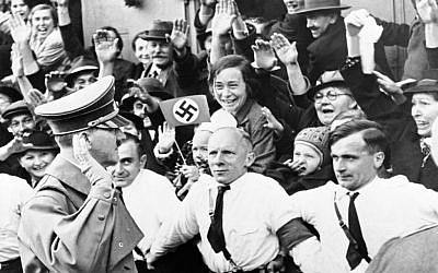 Illustrative: An Associated Press photograph shows Adolf Hitler, German Reichsfuehrer, acknowledging the ecstatic cheers of Sudeten Germans, as he entered Asch, on the heels of German armies which took over the ceded Czechoslovakian territory, on October 3, 1938. The AP caption notes: 'Party members grip each other's belt, straining to hold the enthusiastic crowds in check.' (AP Photo)