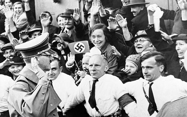 An Associated Press photograph shows Adolf Hitler, German Reichsfuehrer, acknowledging the ecstatic cheers of Sudeten Germans, as he entered Asch, on the heels of German armies which took over the ceded Czechoslovakian territory, on October 3, 1938. The AP caption notes: 'Party members grip each other's belt, straining to hold the enthusiastic crowds in check.' (AP Photo)