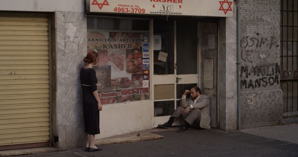 In a scene from Daniel Burman's 'The Tenth Man,' actors Alan Sabbagh and Juliata Zylbeberg in front of a kosher butcher shop. (courtesy)