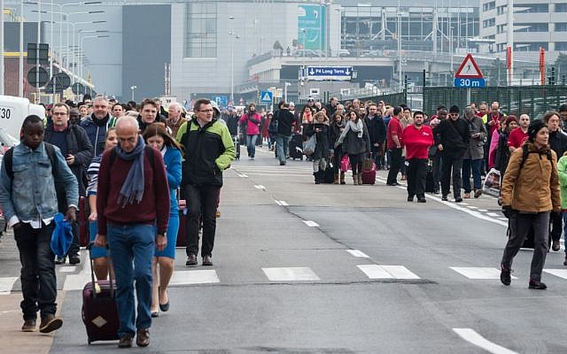 People walk away from Brussels airport after explosions rocked the facility in Brussels, Belgium, March 22, 2016. (AP/Geert Vanden Wijngaert)