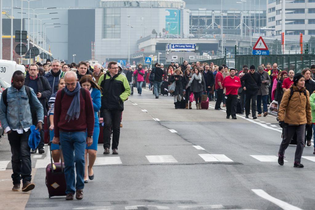 People walk away from Brussels airport after explosions rocked the facility in Brussels, Belgium, March 22, 2016. (AP/Geert Vanden Wijngaert)