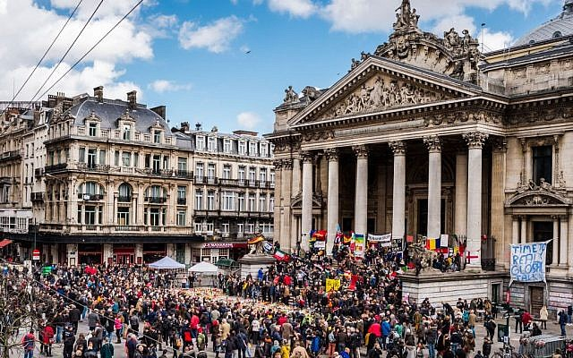 People gather at a memorial site at the Place de la Bourse in Brussels, Sunday, March 27, 2016. In a sign of the tensions in the Belgian capital and the way security services are stretched across the country, Belgium's interior minister appealed to residents not to march Sunday in Brussels in solidarity with the victims. (AP Photo/Geert Vanden Wijngaert)