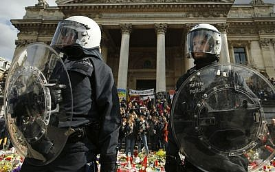 Police in riot gear protect one of the memorials to the victims of the recent Brussels attacks, as right wing demonstrators protest near the Place de la Bourse in Brussels, Sunday, March, 27, 2016. (AP Photo/Alastair Grant)
