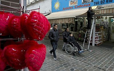 People pass a shop in the Molenbeek neighborhood of Brussels, Belgium, Saturday, March 19, 2016, where fugitive terror suspect Salah Abdeslam was arrested after a four-month manhunt. (AP Photo/Peter Dejong)