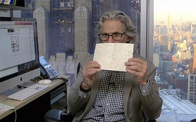 New Yorker cartoon editor Bob Mankoff in his office holding a letter from Rabbi Jill Jacobs' daughter. (Screenshot from The New Yorker via JTA)