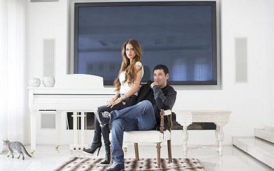 Gilbert Chikli, 50, and his wife, Shirly Chikli, 31, pose at their home in Ashdod on March 28, 2016. (AP/Oded Balilty)