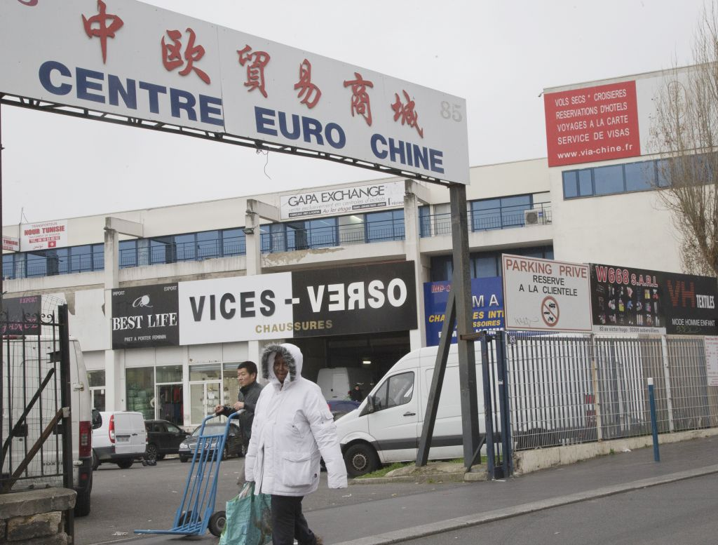 "In this Wednesday, Feb. 24, 2016, photo, people walk in a Chinese wholesale clothing district in Aubervilliers, north of Paris, France. France's financial crimes squad in June busted a money transfer network in Aubervilliers, where Chinese merchants are accused of laundering money for North African drug dealers. Sign in Chinese reads ""China Europe Trade and Commerce City"". (AP Photo/Jacques Brinon)"