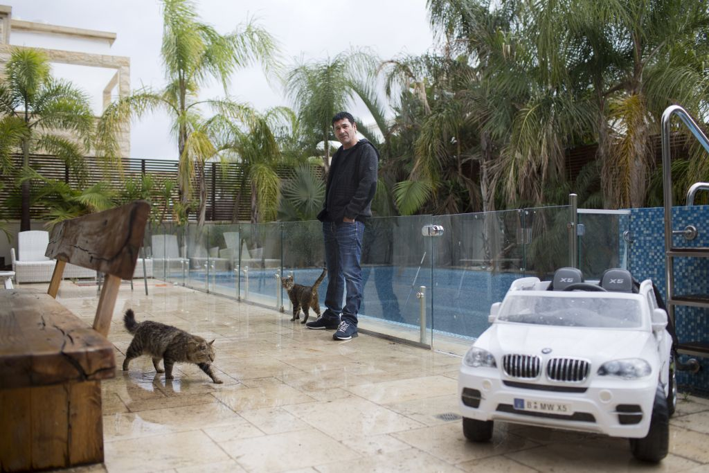 Gilbert Chikli, 50, poses for a photo at his home in Ashdod, Israel, Monday, March 28, 2016. Chikli, a visionary fraudster, ripped off some of the world's biggest corporations, and then laundered millions in China, which is serving as a massive money laundering machine for foreign criminals, an AP investigation has found. (AP Photo/Oded Balilty)