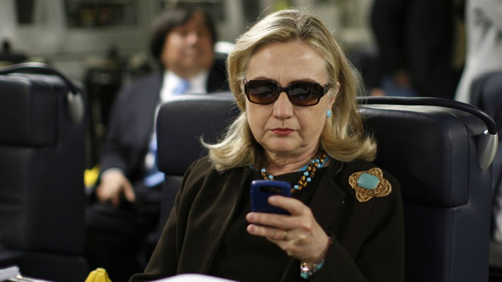 In this Oct. 18, 2011, file photo, then-secretary of state Hillary Clinton checks her Blackberry from a desk inside a C-17 military plane upon her departure from Malta, in the Mediterranean Sea, bound for Tripoli, Libya. (AP Photo/Kevin Lamarque, Pool, File)