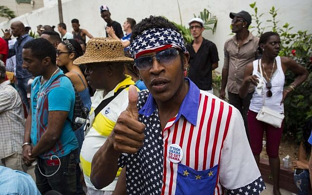 A man wearing a shirt and head scarf with a Stars and Stripes motif flashes a thumbs up at a weekly rumba dance gathering in Havana, Cuba, Saturday, March 19, 2016. (AP Photo/Desmond Boylan)