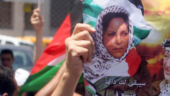 Palestinians hold posters showing Dalal Mughrabi, a Palestinian terrorist involved in the 1978 Coastal Road Massacre in which 38 Israelis were killed, in the West Bank city of Ramallah, on July 16, 2008. (Issam Rimawi/Flash90)