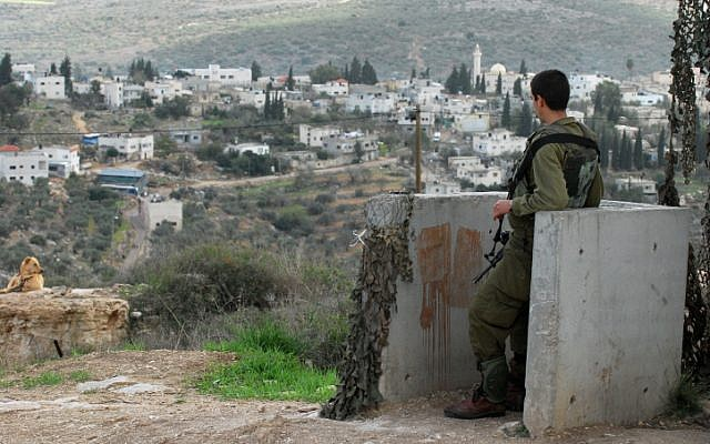 Illustrative image of an Israeli soldier guarding near the Kedumim settlement, with the Palestinian village of Kadum in the background, on November 13, 2009. (Gili Yaari/Flash90)