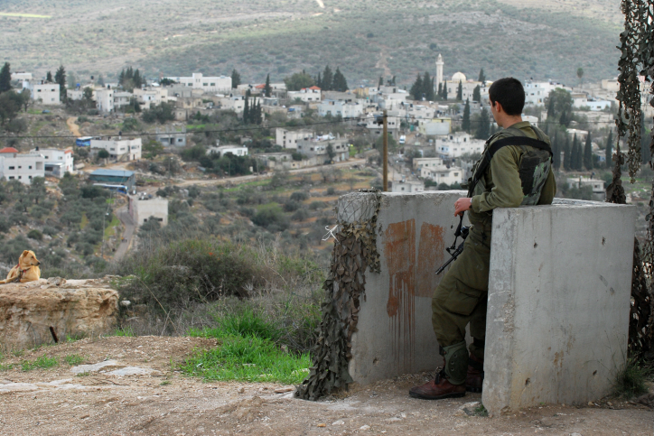 File. An Israeli soldier guarding near the Kedumim settlement, with the Palestinian village Kadum in the background, on November 13, 2009. (Gili Yaari/Flash90)