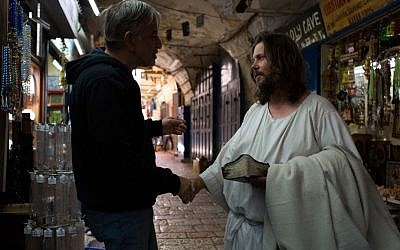 A man dressed as Jesus Christ greets a storeowner in the Old City of Jerusalem on May 13 2013. (Sarah Schuman/ Flash90)