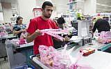A supermakert worker bagging groceries in plastic bags at the Rami Levi supermarket in Talpiot, Jerusalem, September 3, 2013. (Yonatan Sindel/Flash90)