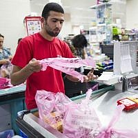 A supermakert worker bagging groceries in plastic bags at the Rami Levi supermarket in Talpiot, Jerusalem, September 3, 2013. (Yonatan Sindel/Flash90)