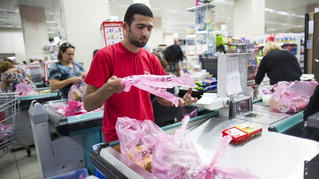 A Supermakert Worker Bagging Groceries In Plastic Bags At The Rami Levi Supermarket Talpiot