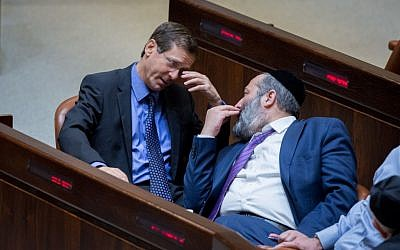 Zionist Union leader Isaac Herzog (L) talks to Shas party leader Aryeh Deri in the Knesset plenum on May 4, 2015 (Miriam Alster/Flash90)