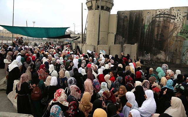 Palestinian women try to cross through the Qalandiya checkpoint on their way for Friday prayers at al-Aqsa Mosque, June 26, 2015. (Flash90)