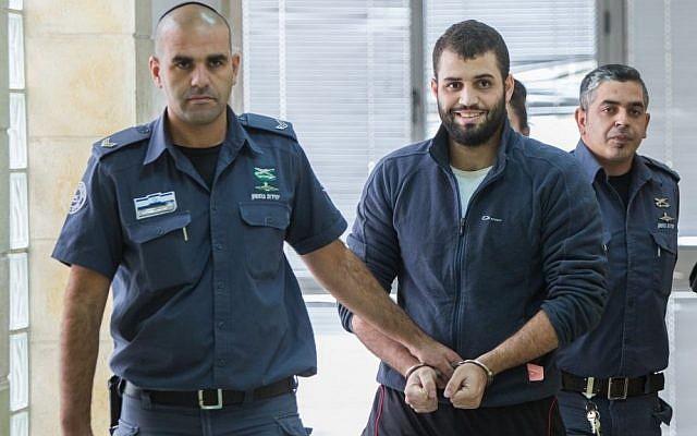 Bilal Abu Ghanem, 21, is escorted by Israeli prison officers outside the Jerusalem District Court  on November 9, 2015. (Yonatan Sindel/Flash90)
