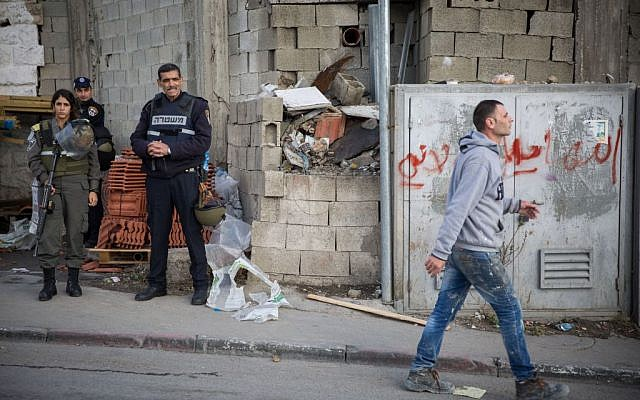 Illustrative: A Palestinian man walks past Israeli police officers at the entrance to the Shuafat refugee camp in East Jerusalem on December 2, 2015. (Hadas Parush/Flash90)