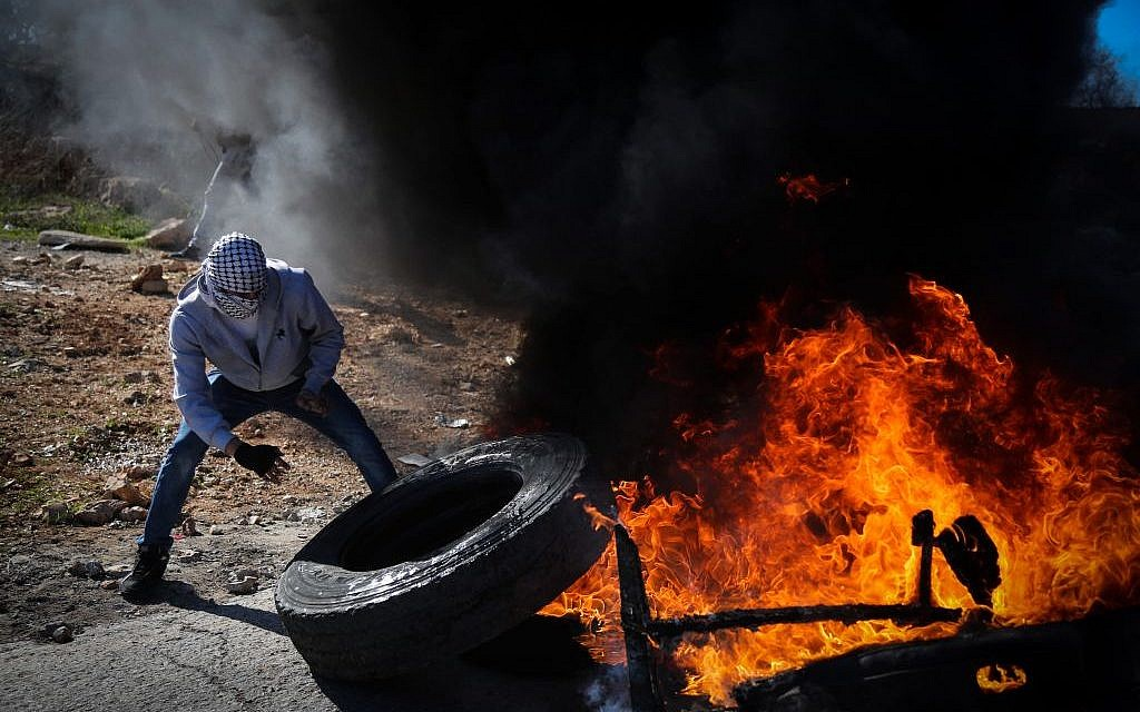 Palestinian protesters burn tires and hurl stones towards Israeli troops during clashes in Aboud village, near the West Bank city of Ramallah on December 5, 2015. (FLASH90)