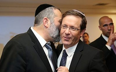 Aryeh Deri, left, whispering to Isaac Herzog at a party in Jerusalem on December 23, 2015. (Yaacov Cohen/FLASH90)
